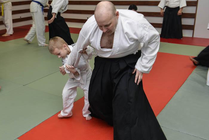 Dziecko i dorosły współnie ćwiczą technikę Aikido