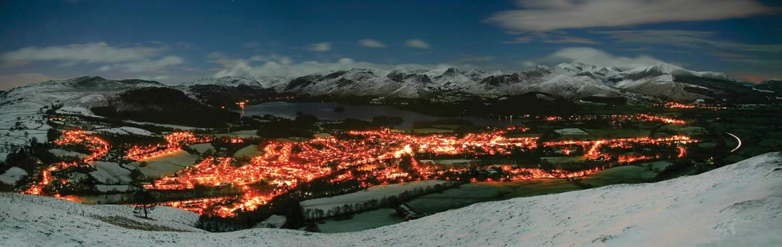 From Latrigg the lights of Keswick resemble lava in a volcano. Stitched panorama of 4 x 25 second exposures. There was a full moon and snow on the ground making the whole scene relatively bright. Canon Rebel with 17-85mm at 24mm, ISO 100, 4 x 25 secs at f/5, tripod. © Stuart Holmes 2014