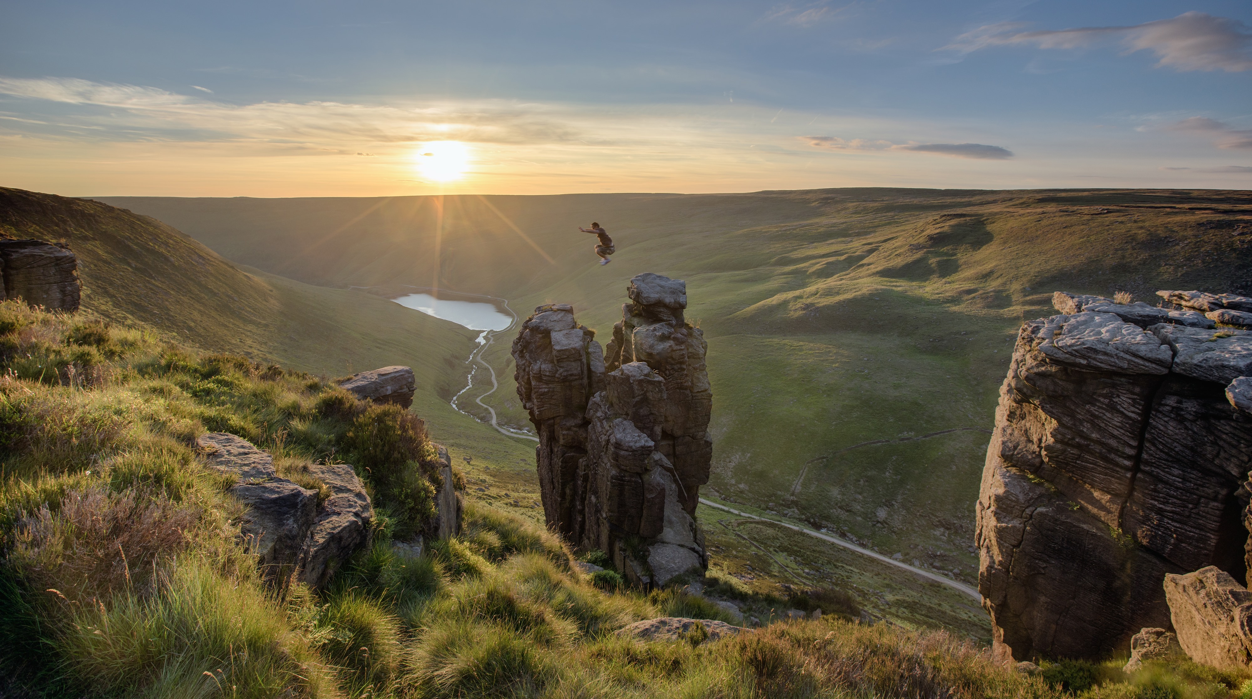man jumping from pinnacle above a lake as the sun sets.