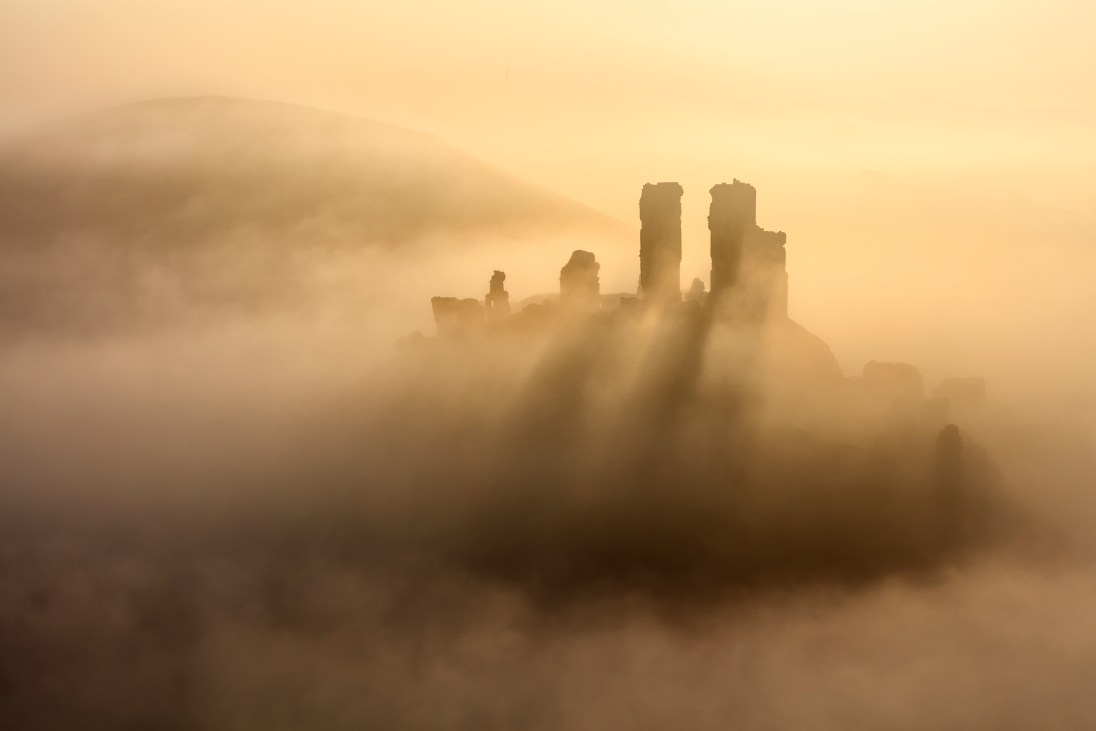 Corfe Castle, backlit in mist on an October morning.Canon 5Ds, 70-300mm f/4-5.6L at 78mm, ISO 100, 1/800 second at f/8. © Mark Bauer