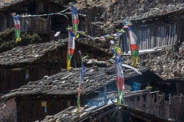 Prayer flags and rooftops at Yangma Village. Canon 5D MkIII, 70-300mm at 207mm, ISO 100, 1/60 sec at f/10. © Stuart Holmes.