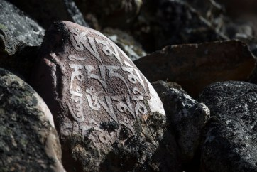 Carved prayer stones called mani stones, often many of these making up a mani wall. Canon 5D MkIII, 70-300mm at 214mm, ISO 100, 1/400 sec at f/6.3. © Stuart Holmes.