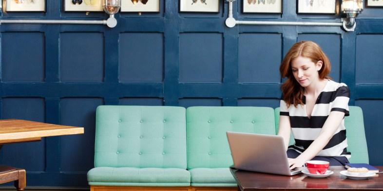 Woman working on laptop in coffee shop