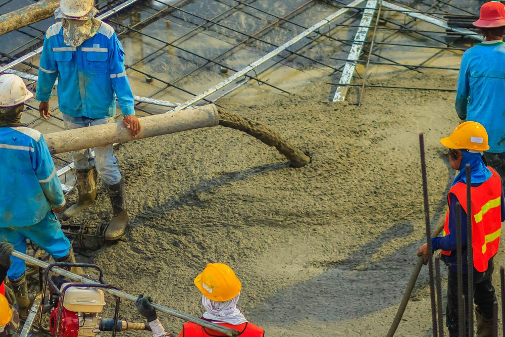 Construction workers are pouring concrete in post-tension flooring work. Mason workers carrying hose from concrete pump or also known as elephant hose during concreting work at construction site