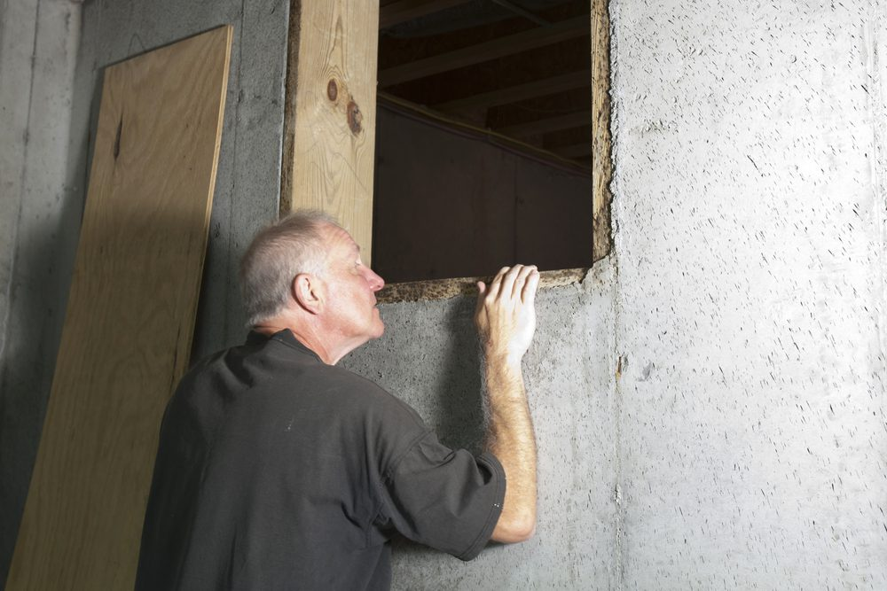 Man looking into crawl space under house