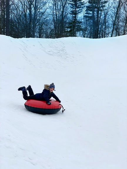 Little boy snow tubing in the snow