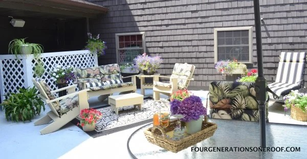 Patio adirondack chairs and sofa, floral patio cushions, white vinyl privacy screen for AC units