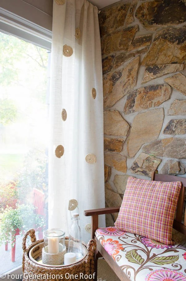 white burlap curtains with sisal roping detail, stone wall, slider door, wood bench, pink plaid pillow, pink flower bench cushion, sisal basket, candles