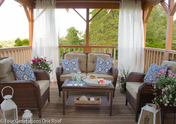 deck with outdoor curtain rod, outdoor curtains, brown wicker furniture and blue throw pillows
