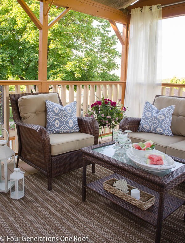 deck with outdoor curtain rod and outdoor white grommet style curtains, brown wicker outdoor furniture