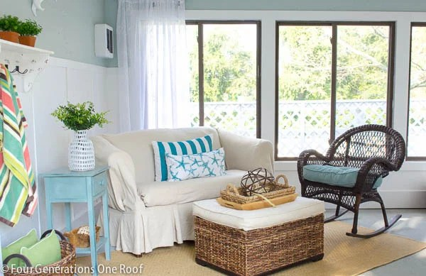 white slipcovered sofa, seagrass ottoman, brown wicker rocking chair, blue and white wall board and batten, striped pool towel, outdoor tan rug