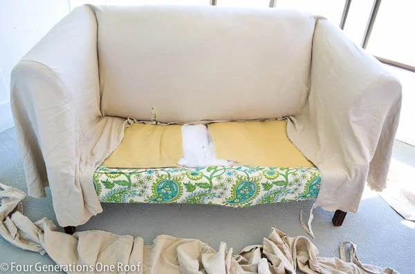 pottery barn white slipcover cut in half, cement floor, pool house