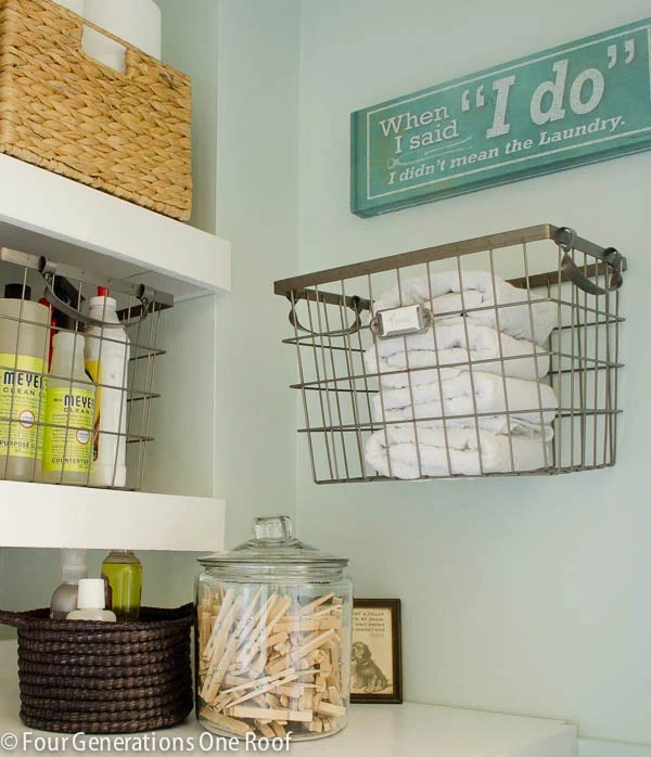 wood floating shelves, wire hanging basket with towels, laundry sign, clothes pins, glass jar, Myers soap, sisal wicker baskets