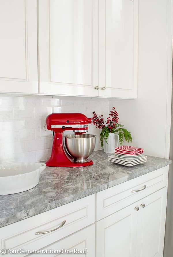 Traditional Christmas Home Tour 2015 -Our Christmas Kitchen 2015: boxwood wreaths, red velvet ribbon, boxwood Christmas tree, red striped hand towel, greens and holly berry.