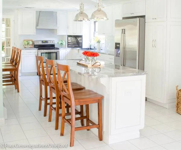 white kitchen, brown Xback counter stools, quartzite countertops, restoration hardware pendants, white tile floor