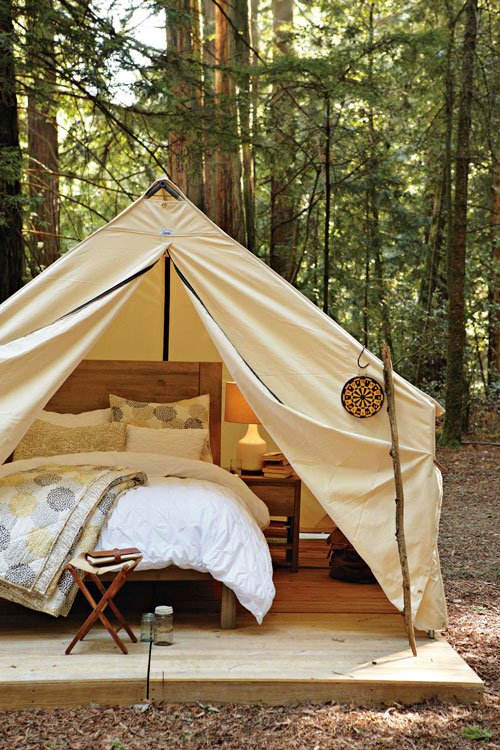 glamping in woods with white tent, queen bed, plywood floor
