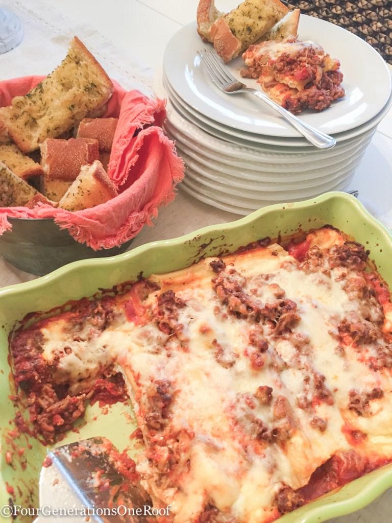 manicotti with hamburger in green casserole dish, white plates and garlic bread