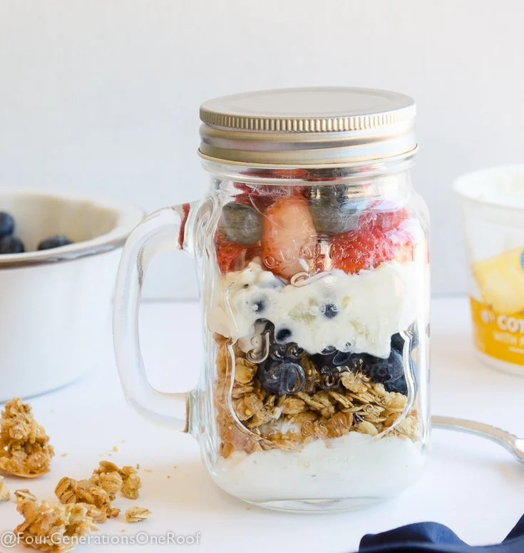 Mason jar filled with cottage cheese, granola, blueberries, strawberries