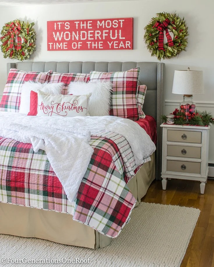red and white Christmas plaid bedding | Christmas bay leaf wreaths | It's the most wonderful time of year sign | gray tufted headboard | Popcorn area rug