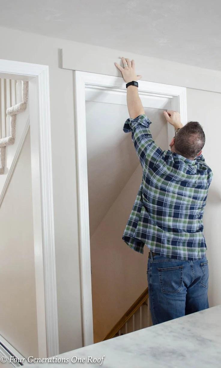 Men installing header for sliding door hardware White basement kitchen door Barn Door Installation without Removing Door Trim