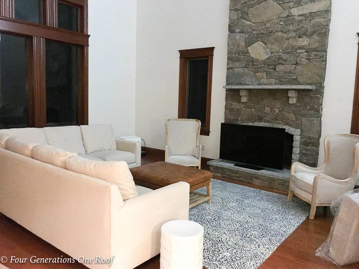 living room before with granite stone mantel, white sectional, blue rug, stained window trim, white accent chairs