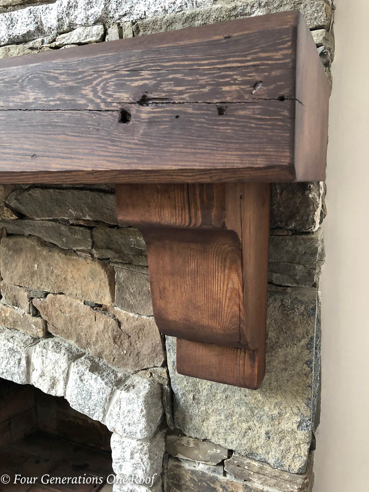 100 year old southern yellow pine beam mantel and corbels being screwed to mantel, stone fireplace