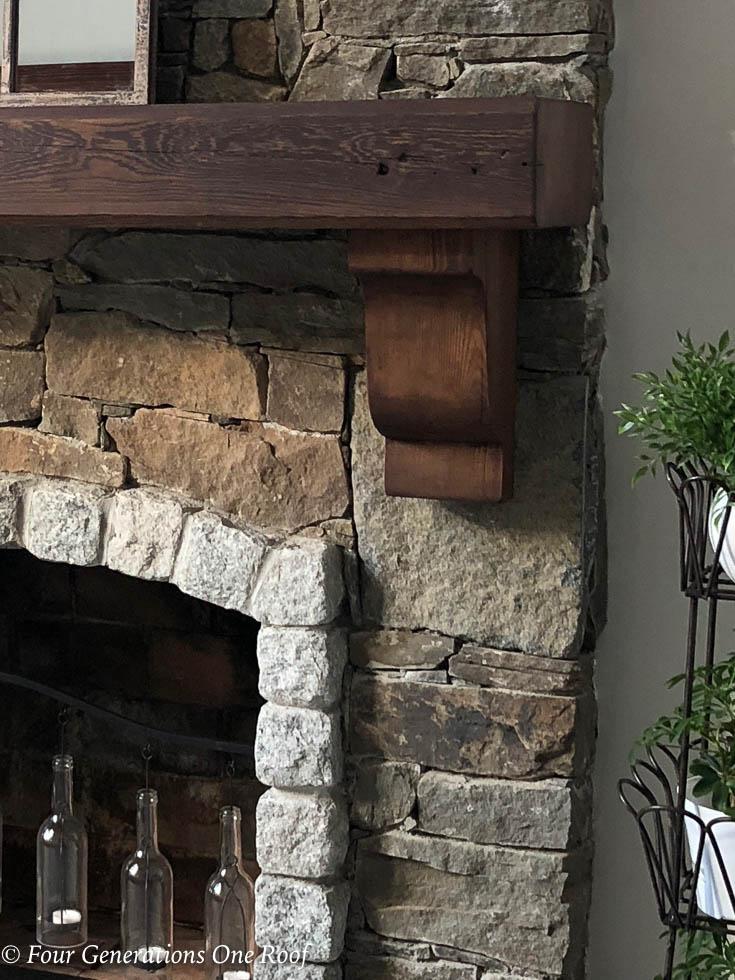 Stone fireplace, dark brown wood mantel,