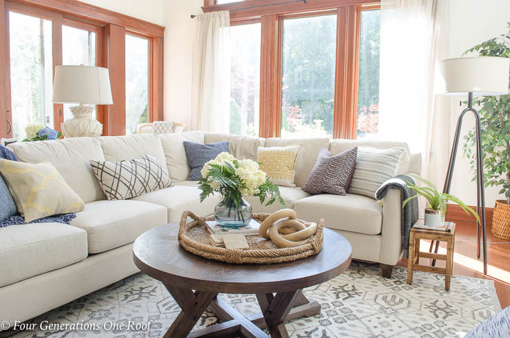 How to Create a Rustic Modern Living Room with 50 foot ceilings | Rustic Modern Living Room with Wood beam Mantel + 50 foot ceilings + large white sectional + Cognac Stained trim and stained baseboard