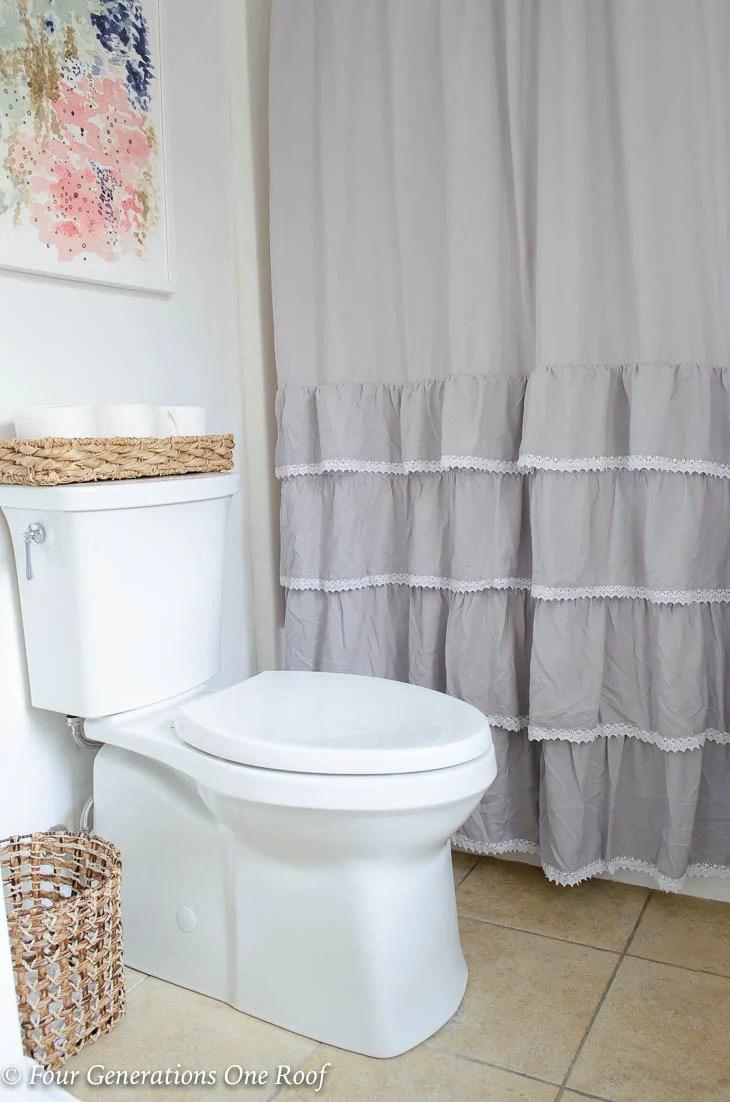 Narrow Bathroom Kohler ContinuousClean Soft Close toilet, gray shower curtain