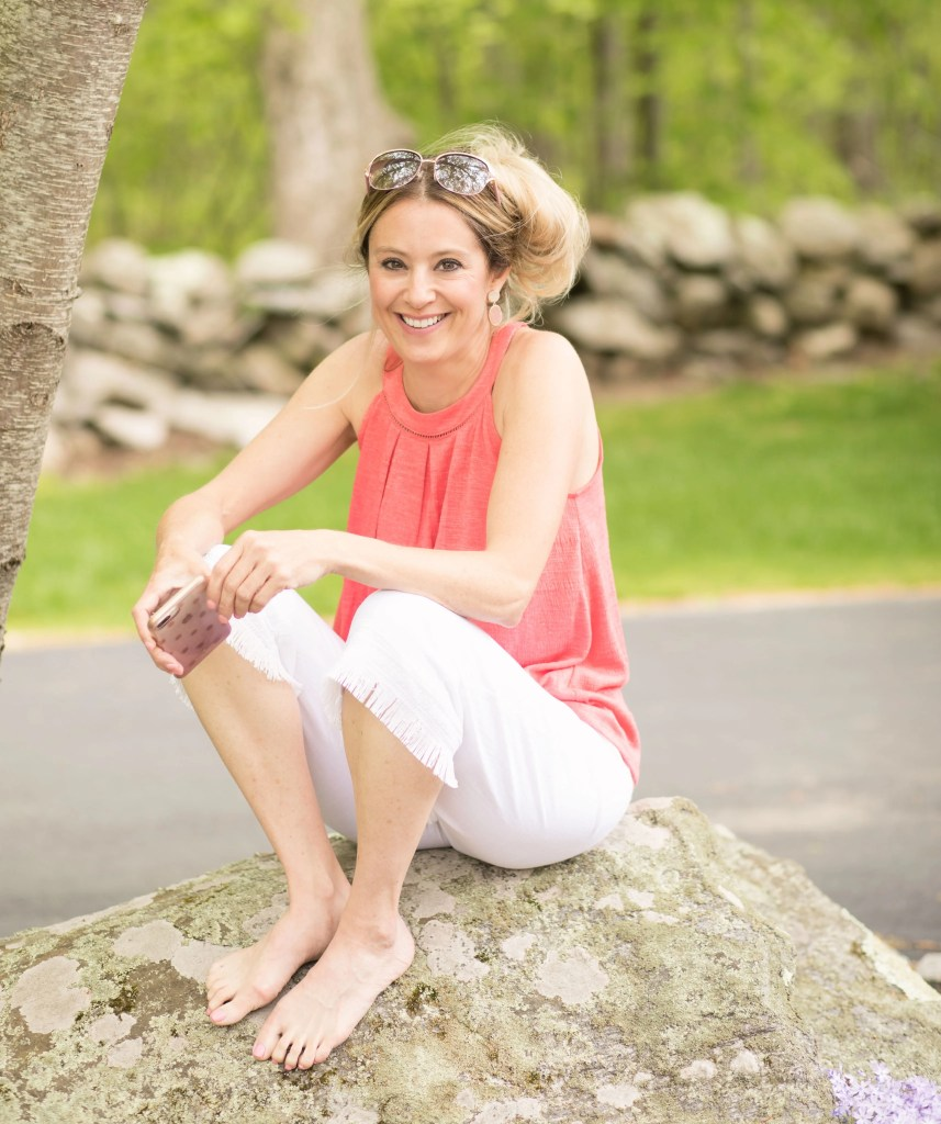 jessica bruno orange top, white pants sitting on rock tips to increase energy