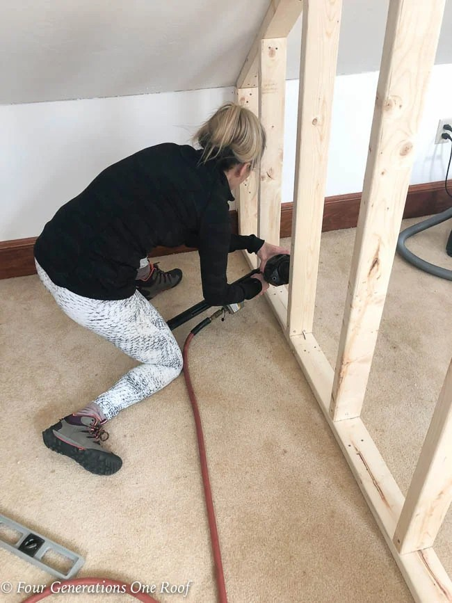 """Jessica Bruno nailing 2x4's every 16"""" on center to create a closet wall"""