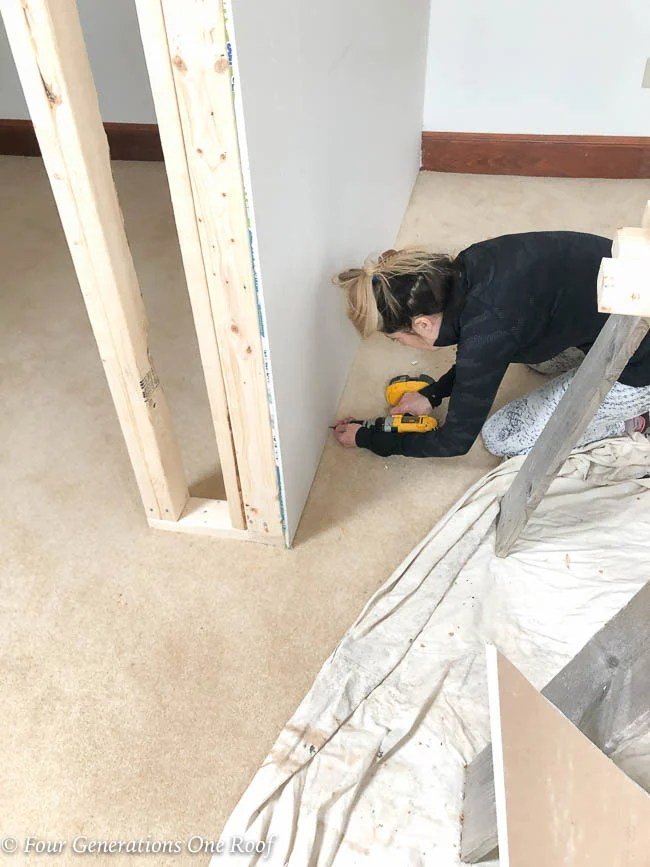 Jessica Bruno screwing drywall to the 2x4 frame closet wall