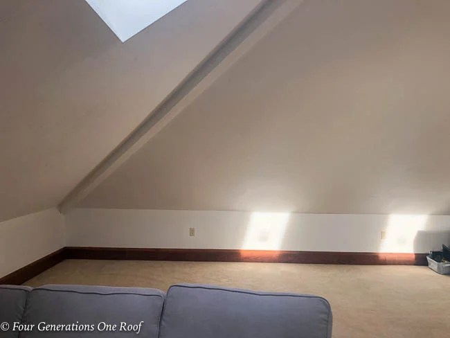 empty loft with slanted ceiling, sky light window, beige carpet and sectional