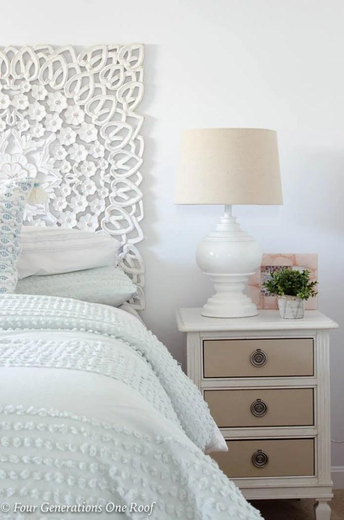 fluffy comforter, white scroll headboard, mint green bedding, mint green comforter, white night table, white lamp, blue tassel throw pillow, green plant