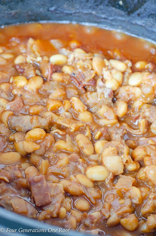 crockpot baked beans with sausage in black crockpot dish