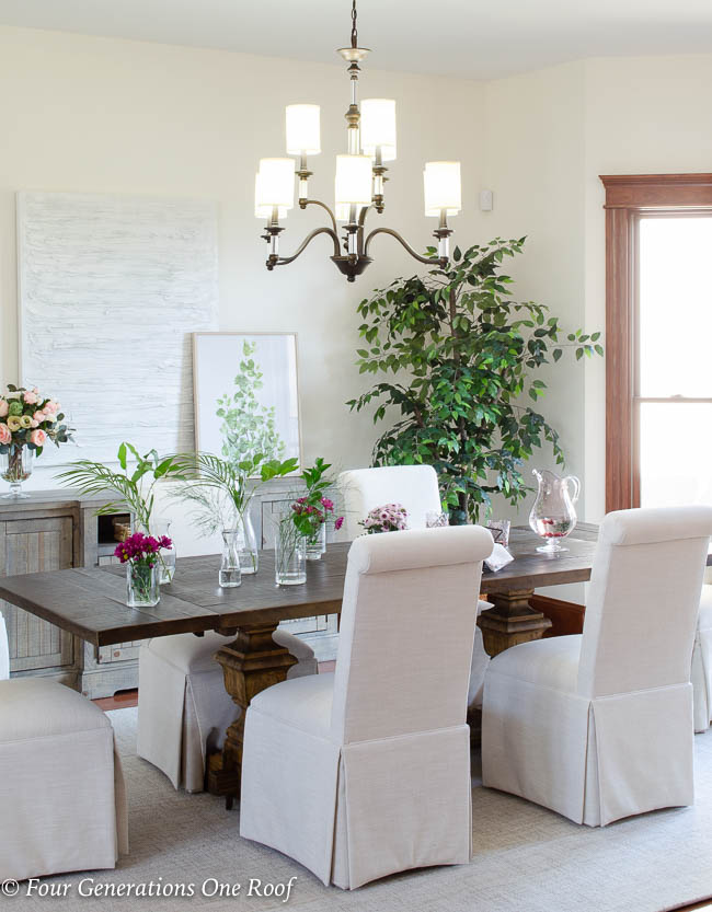 Arhaus dining table, slipcovered parson chairs, lighting updates in our home with Hinkley Modern Traditional Chandelier, greenery, Dash and Albert off white wool rug