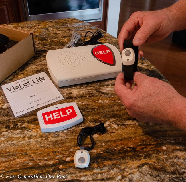 Bay Alarm Medical with Senior Citizen holding help button, wristband and necklace with fall detection