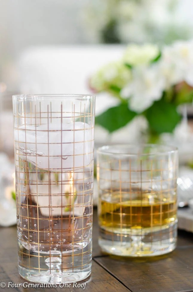 gold checkered glassware, dark wood table, flowers in vase