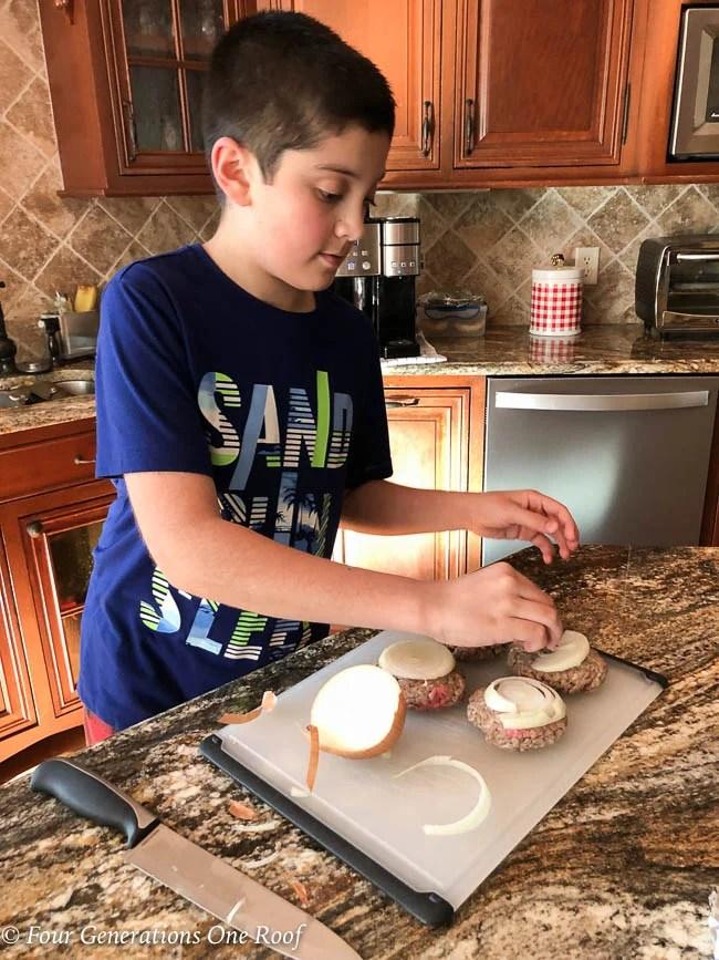 Multigenerational family, grandson making dinner for his grandparents, fatty hamburger bacon onion on stovetop