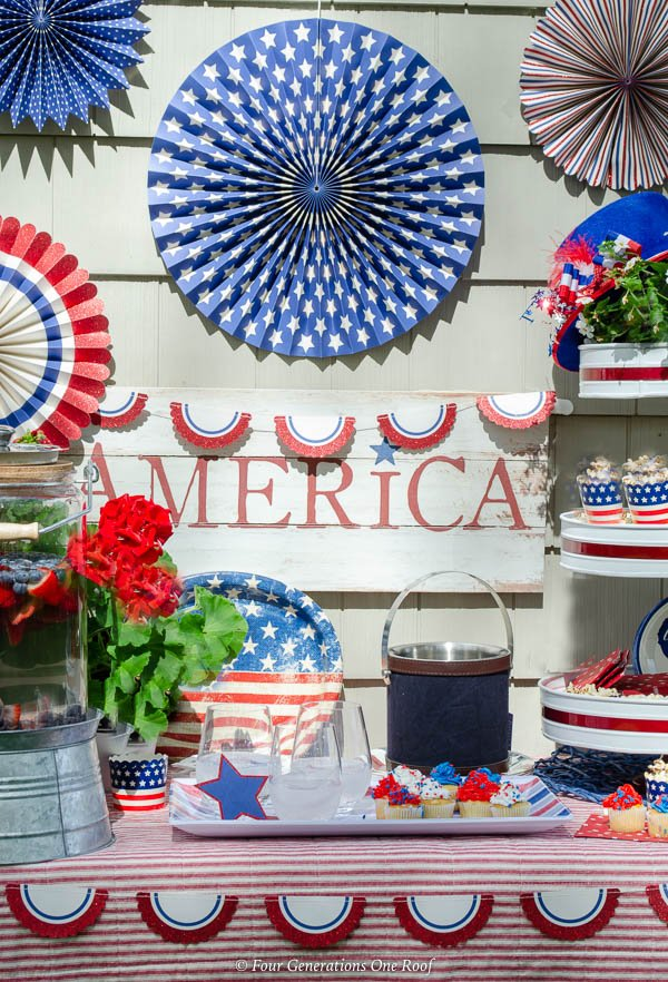 patriotic beverage station with patriotic bunting, patriotic banners, white and red 3 tier tray with popcorn, striped platter, red striped tablecloth, American Sign, patriotic fans