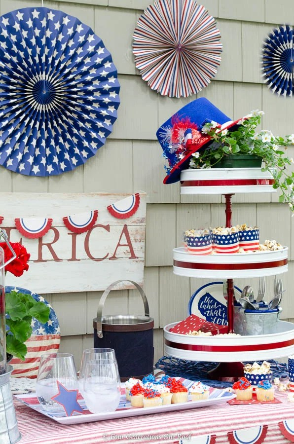 Classy Patriotic Decor Ideas on our Patio patriotic beverage station with patriotic bunting, patriotic banners, white and red 3 tier tray with popcorn, striped platter, red striped tablecloth, American Sign