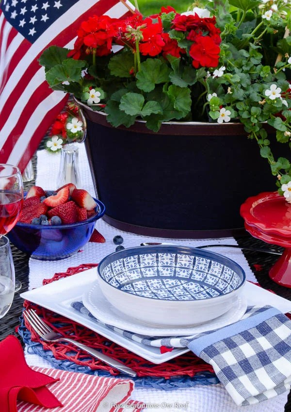 patriotic outdoor table on law, ice bucket centerpiece filled with geraniums and flags, red striped tablecloth, melamine blue and white dishes, wine glass filled with red wine