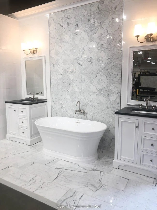 white bathroom vanity, black granite counter, white quartzite wall tile, white soaking tub