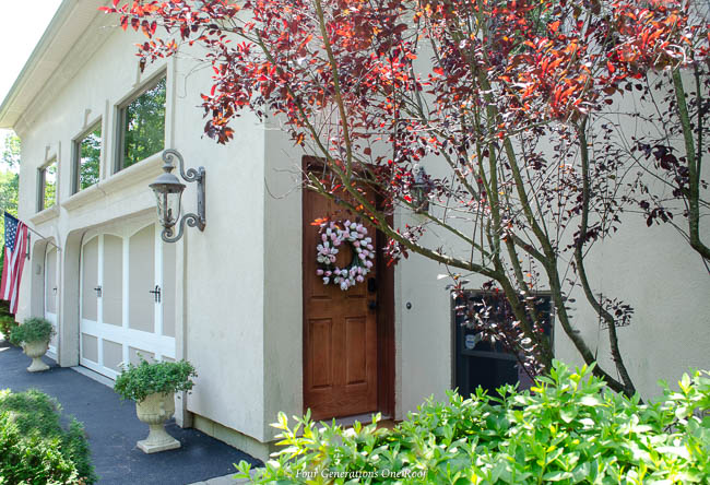 cherry stain side entrance garage door, wreath, 3 car garage,