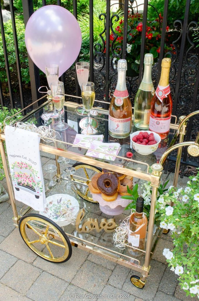 bridal shower bar cart with champagne, pink balloon, donut cake, raspberries and plant
