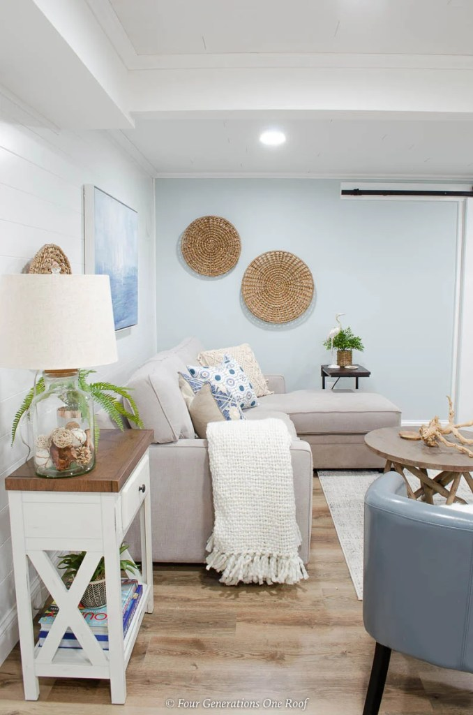 white plank wall, grey couch, blue medallion pillow, seagrass wall accent, coastal wall art, blue walls