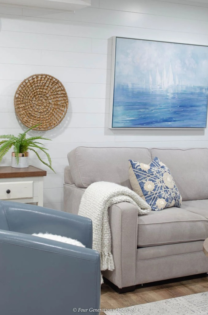 white plank wall, grey couch, blue medallion pillow, seagrass wall accent, coastal wall art