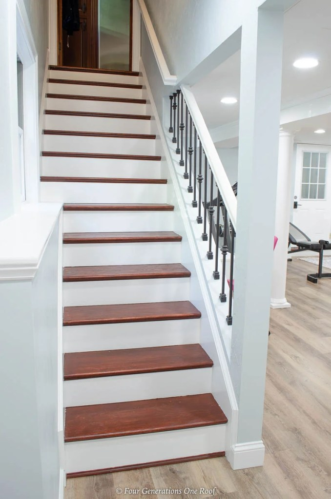 open staircase in a basement with iron balusters, harvest oak vinyl plank flooring, blue walls