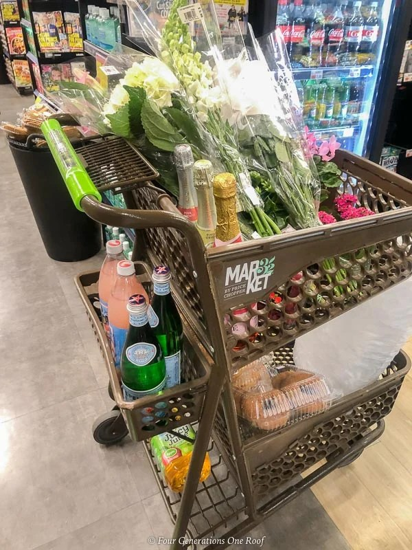 bridal shower grocery shopping cart filled with flowers, champagne and donuts