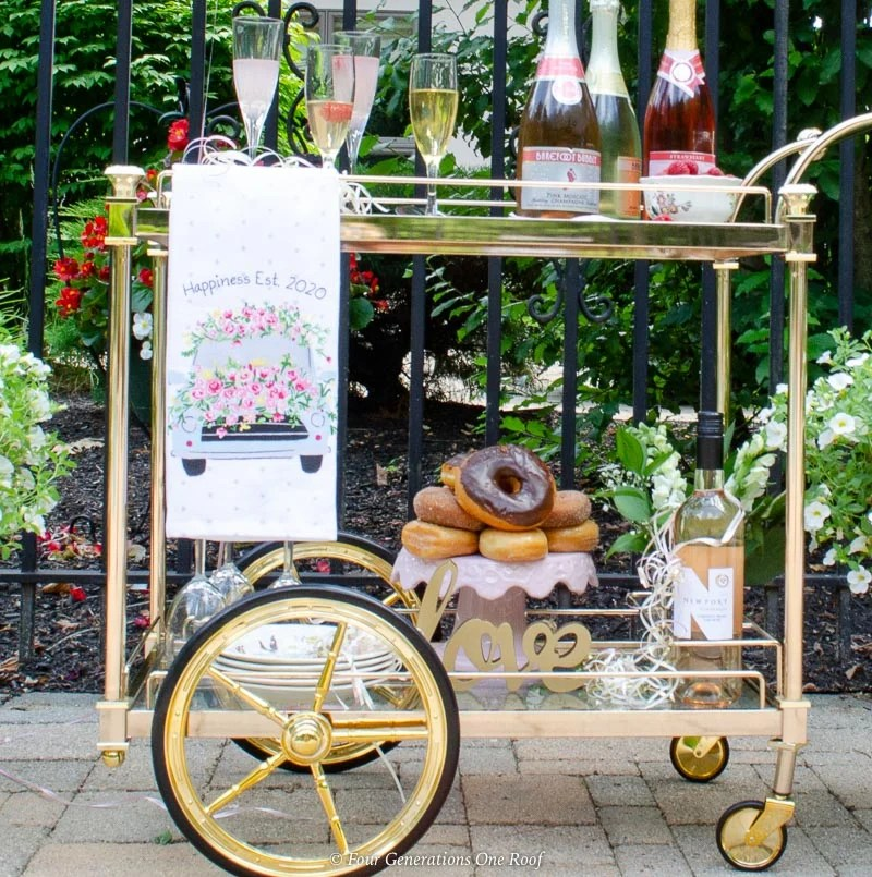 patio rose gold bar cart, champagne, donut cake, pink balloon